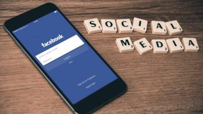 Mobiles Telefon liegt auf dem Tischt. Daneben steht das Wort Social Media.