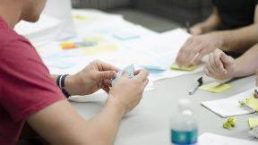 Geschäftsmodelle neu denken. Personen sitzen am Schreibtisch und sammeln gemeinsam Ideen