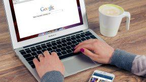 Mann sitzt am Laptop und googel.