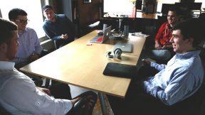 Mitarbeitende sitzen gemeinsam in einem Besprechungszimmer und erarbeiten Ideen aus.