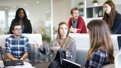 Menschen sitzen im Meeting und unterhalten sich.