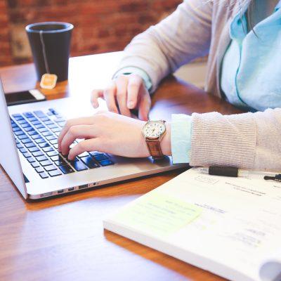 Eine Frau sucht am Laptop nach Online-Seminaren