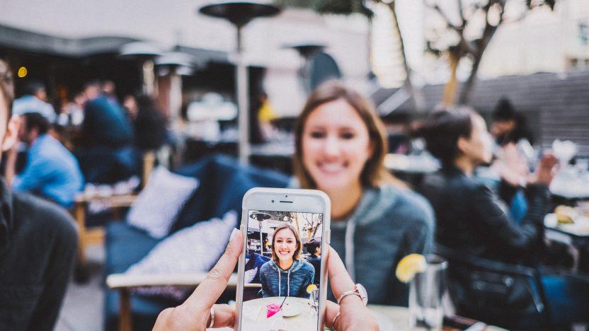 Eine Frau wird in einem Restaurant mit einem Smartphone fotografiert.
