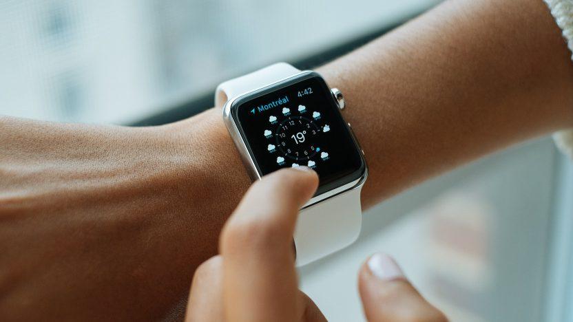 Eine Frau zeigt mit ihrem Finger auf die Uhr an ihrem Handgelenk.
