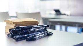 Schwarze Stifte und Blöcke liegen auf einem Tisch, um Ideen zu symbolisieren.