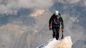 Bergsteiger erklimmt Gipfel.