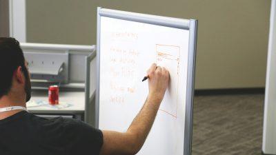 Mann steht vor einem Whiteboard und schreibt Strategien nieder