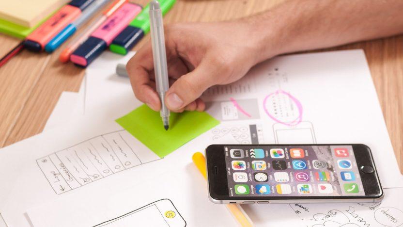 Auf dem Tisch liegen ein Smartphone, Notizzettel in grün und weitere Analysedaten plus Textmarker. Ein Mann schreibt.