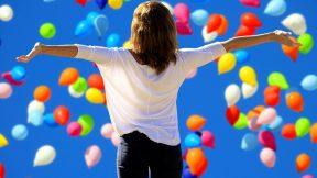 Eine Frau freut sich und badet in Luftballons.
