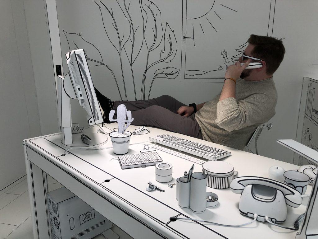Ein Mann sitzt in einem Büro. Er telefoniert mit einer Banane. Die Kulisse ist schwarz-weiß und sieht aus, wie eine Bleistiftzeichnung.