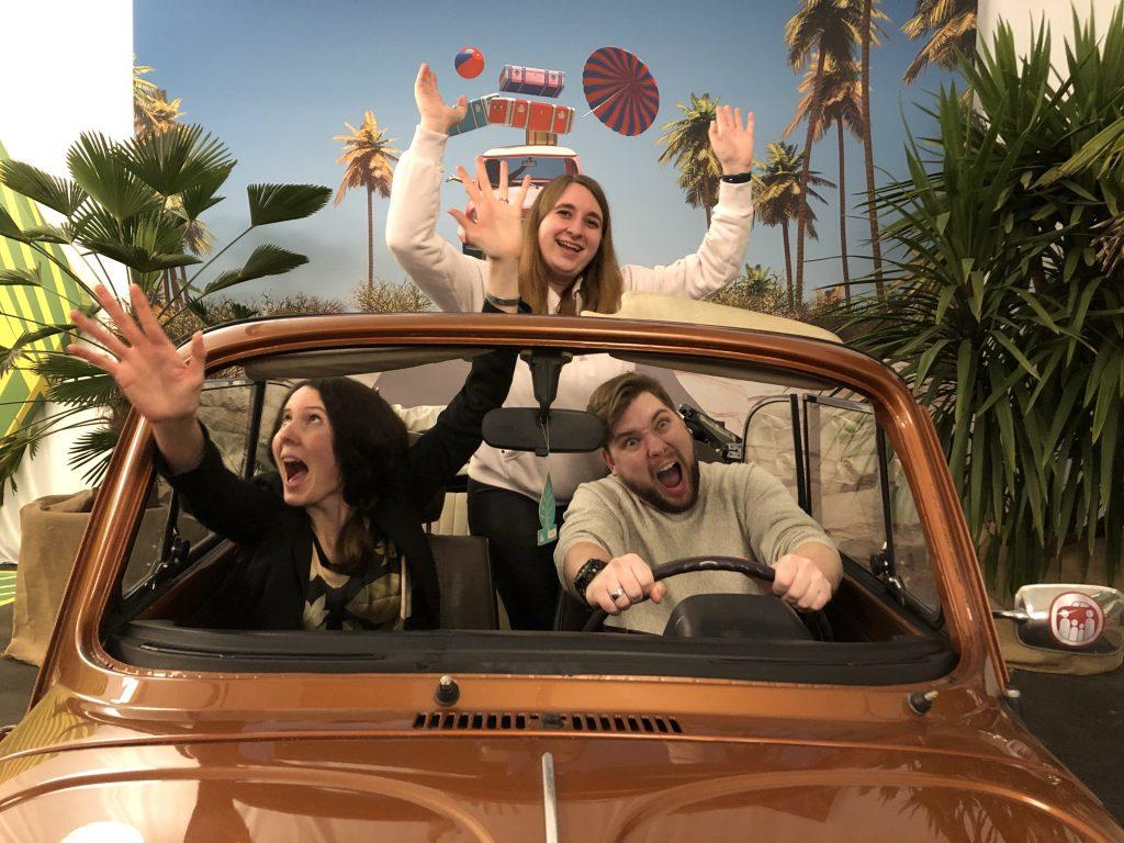 Zwei Frauen und ein Mann sitzen in einem alten, bronzefarbenen VW-Käfer. Sie tun so, als ob sie gerade von einem anderen Auto verfolgt werden. Ihre Mimik sieht lustig aus.