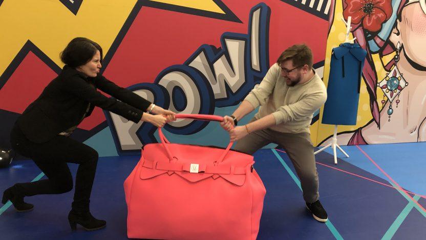 Zwei Personen streiten sich um eine große, pinke Handtasche.