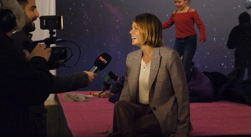Die Schauspielerin Jessica Schwarz sitzt auf einem rosa Teppich, der zu ihrer Mitmach-Kulisse gehört. Sie wird gerade interviewt.