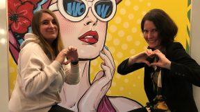 Zwei Frauen sitzen vor einer Pop-Art-Kulisse und machen ein Selfie.