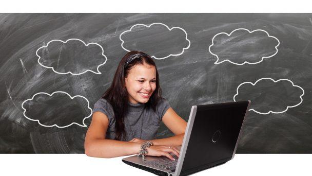 Eine junge Frau sitzt vor dem Laptop. Die junge Frau Freut sich. Im Hintergrund ist eine Tafel.