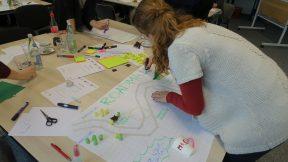 Eine junge Frau schreibt ihre Ideen auf ein großes Blatt Papier.