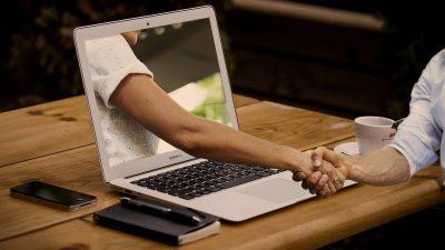 Auf dem Foto schütteln sich zwei Menschen die Hand. Eine Person sitzt vor dem Laptop und die andere Person streckt den Arm aus dem Laptop.