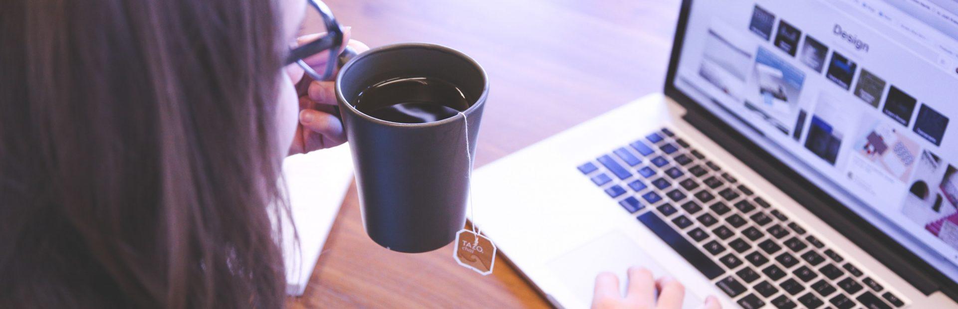 Frau sitzt am Laptop, trinkt eine Tasse Tee und arbeitet in Homeoffice.