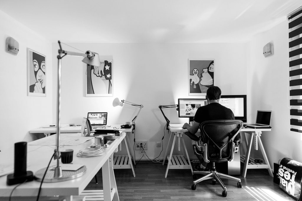 Ein Mann arbeitet von zu Hause aus an einem Schreibtisch.