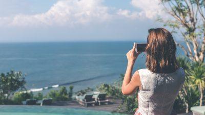 Eine Frau fotografiert mit ihrem Smartphone das Meer