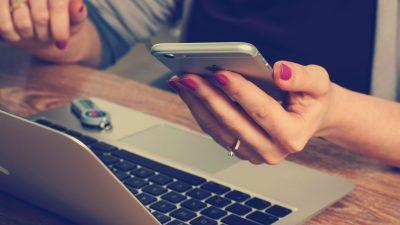 Frau sitzt im Büro mit Laptop und Smartphone in der Hand.