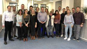 Isahr-Immobilien-Mitarbeitende und Mitarbeitenden von Mittelstand 4.0-Kompetenzzentrum Kommunikation posieren für ein gemeinsames Foto.