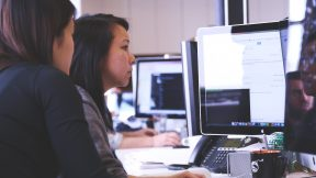 Zwei Frauen sitzen an einem digitalen Arbeitsplatz und arbeiten am Computer.