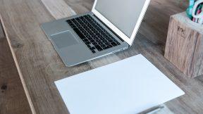 Ein grauer Laptop steht neben einem Stapel Papier und einem Stiftehalter.