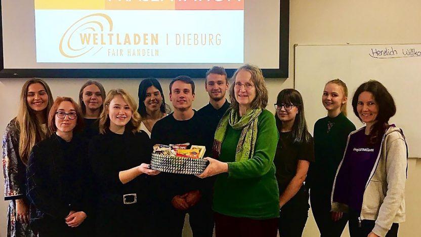 In der Hochschule Darmstadt stehen Studierende gemeinsam mit den Verantwortlichen des Weltladens für ein Foto auf dem Podium.