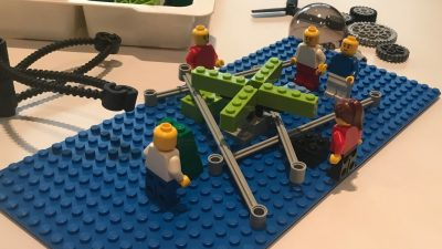 Auf dem Bild sind Lego-Figuren, die zusammen arbeiten.