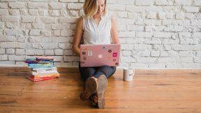 Frau sitzt auf dem Boden an die Wand angelehnt und schaut in ihren Laptop. Auf dem Boden liegen noch Bücher.