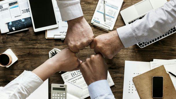 Über einem Schreibtisch klopfen Kollegen ihre Hände in Form einer Faust aneinander: Ein Symbol für gegenseitiges Vertrauen.