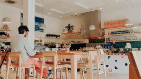 Ein Mann sitzt auf einem Hochstuhl in einem Cafe und arbeitet digital während er einen Kaffee trinkt.