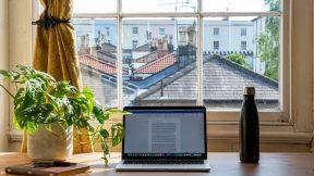 Ein Laptop steht zu Hause auf der Fensterbank. Man blickt dahinter über Häuserdächer.