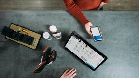 Eine Frau steht an einem Tresen und bezahlt per Smartphone NFC-Technologie