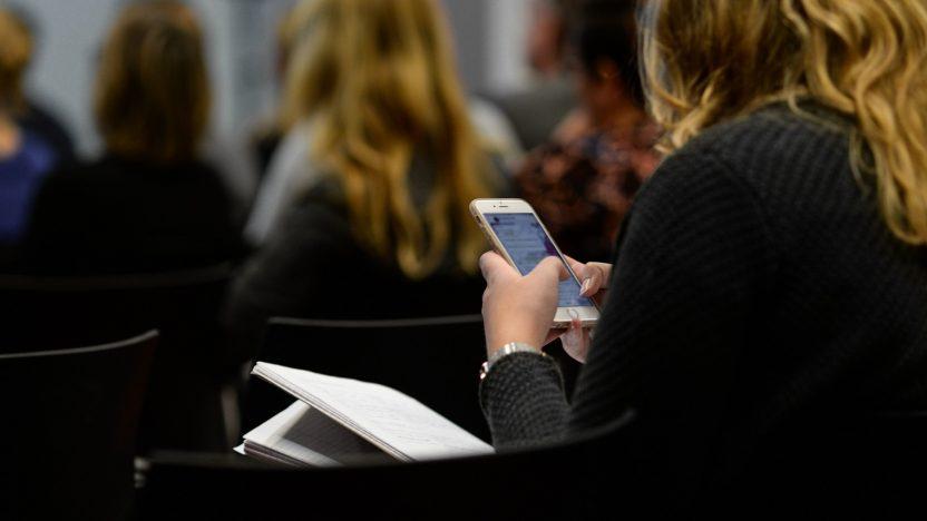 Eine Frau schaut auf einer Veranstaltung sitzend auf ihr Smartphone.