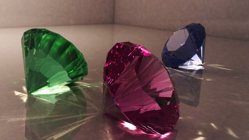 Drei Diamenten in den Farben gün, ros und blau liegen auf dem Boden.