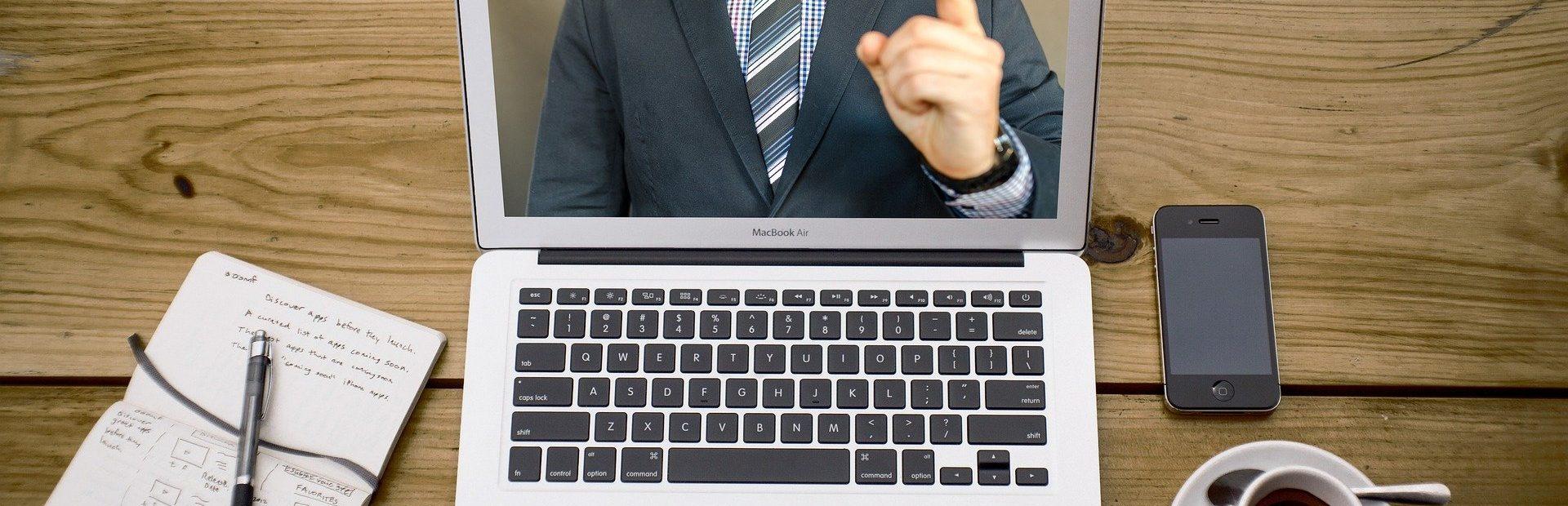 Auf einem Tisch stehen Laptop, Block und Stift, eine Tasse Kaffee und ein Smartphone. Auf dem Laptop läuft eine Videokonferenz.
