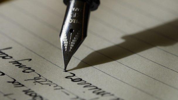 Eine Füllerspitze gleitet über ein liniertes Papier