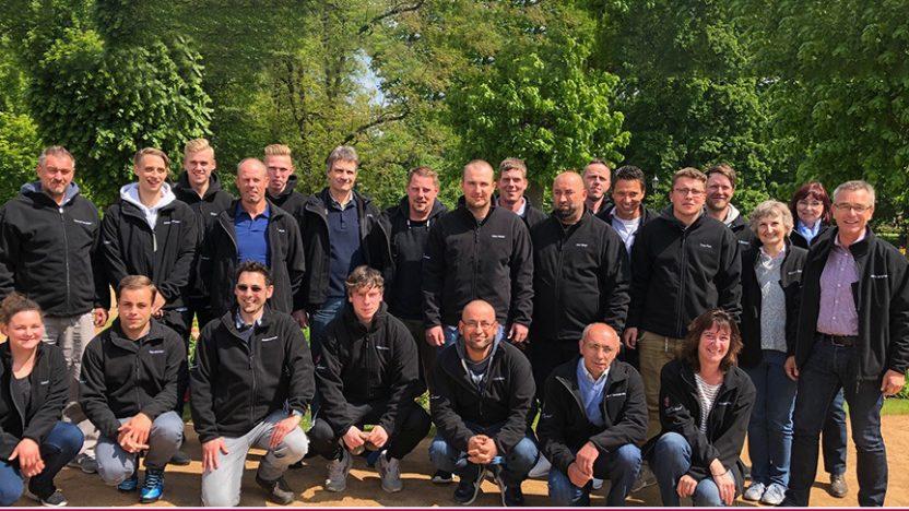 Das Team des Gartenbauunternehmens Borgmann steht im Freien zusammen für ein Gruppenfoto.