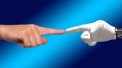 Ein menschlicher Zeigefinger berührt den Zeigefinger einer Roboterhand.