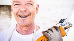 Ein Mann hat eine orange Bohrmaschine in der Hand und lacht.