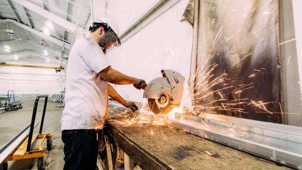 Ein Mann sägt ein Stück Metall.