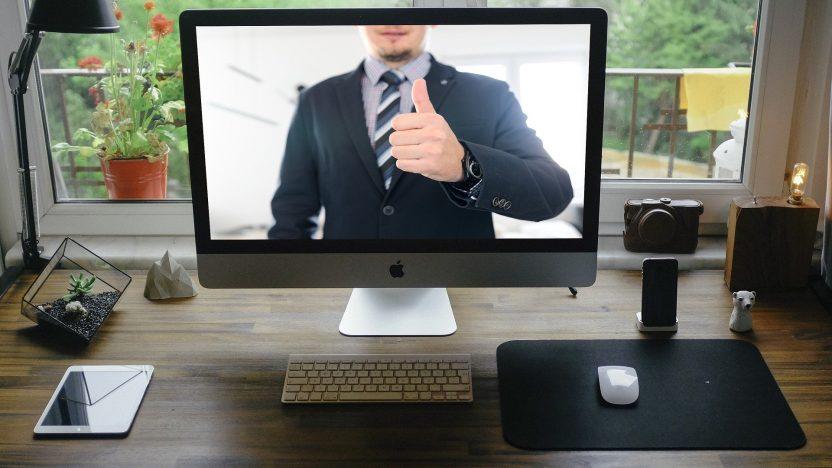 Auf einem Arbeitsplatz-Schreibtisch steht ein Bildschirm. Ein Mann hebt darin seinen Daumen.