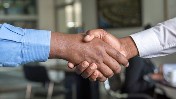 Zwei Menschen geben sich die Hand und vereinbaren eine Zusammenarbeit.