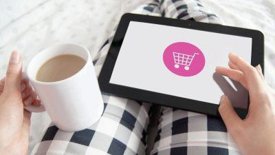 Eine Frau sitzt gemütlich auf dem Sofa und bestellt online über ihr Tablet.