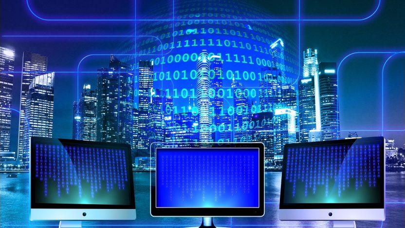 Drei Monitore stehen vernetzt nebeneinander. Im Hintergrund sieht man eine Skyline.