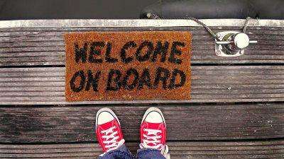 """Digitales Onboarding: Ein Mensch steht vor einer Fußmatte mit der Aufschrift """"Welcome on Board"""""""