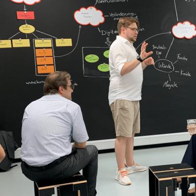 Sebastian Peter erklärt die Funktion des Media-Innovation-Lab vor sitzenden Teilnehmerinnen