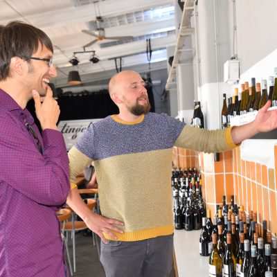 Stefan Voigt und David Zibold vor einem Weinregal.